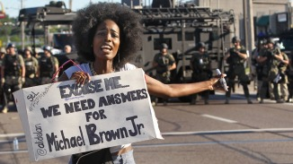 A protester shouts as she moves away from a line of riot police, Ferguson MO, 8/13/14