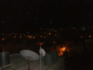 Hebron by night: the view from Leila's roof. Note the water tanks, which aren't found in settlements where Israel provides both electricity and running water. The lights are probably from Kiryat Arba, the enormous settlement outside of town.