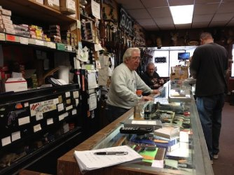 Fred Delia, owner of Delia's Gun Shop in the Wissinoming section, helps a customer